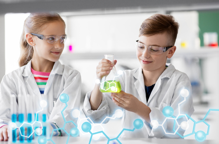 Education, science and children concept - kids with test tubes studying chemistry at school laboratory
