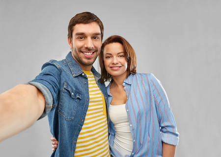 People concept - happy couple hugging and taking selfie over grey background Stock fotó