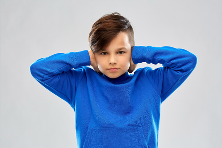 Noise, stress and people concept - stressed boy in blue sweater closing ears by hands over grey background Archivio Fotografico