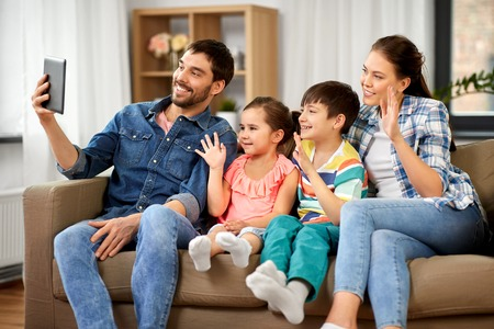 Family and people concept - happy father, mother, little son and daughter having video call on tablet pc computer and waving hand at home Stock Photo