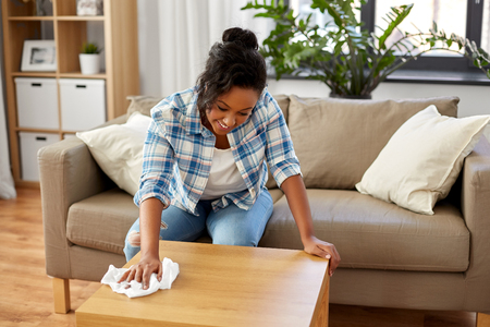 Household, cleaning and people concept - happy African american woman or housewife wiping table by tissue or rag at home