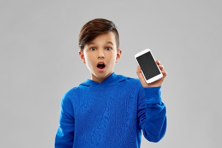 Childhood, technology and people concept - shocked boy in blue hoodie showing smartphone with blank screen over grey background