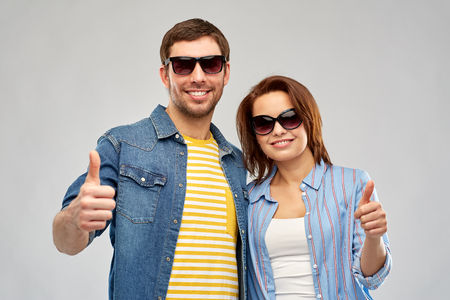 Summer, eyewear and people concept - happy couple in sunglasses showing thumbs up over grey background Stock Photo