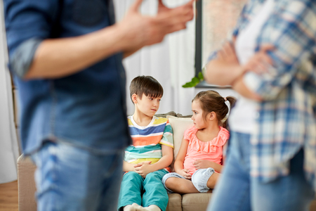 Concepto de problema, conflicto y personas de la familia: niños tristes viendo a sus padres pelearse en casa Foto de archivo