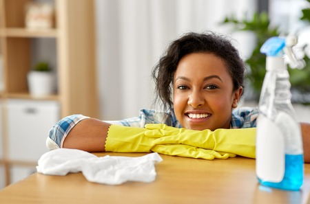 Household, cleaning and people concept - happy African american woman or housewife in rubber gloves with spray detergent and rag at home