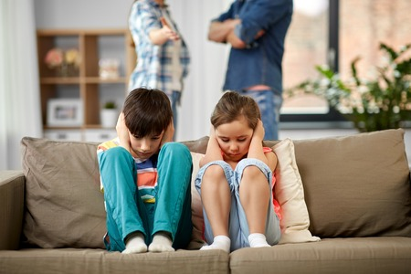 Family problem, conflict and people concept - sad children closing ears while their parents quarreling at home