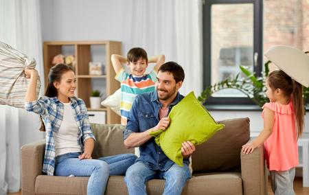 Familien-, Kindheits- und Menschenkonzept - glücklicher Vater, Mutter, kleiner Sohn und Tochter kämpfen mit Kissen und haben Spaß zu Hause
