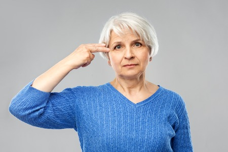 Stress, mental health and old people concept - portrait of senior woman in blue sweater making finger gun gesture over grey background