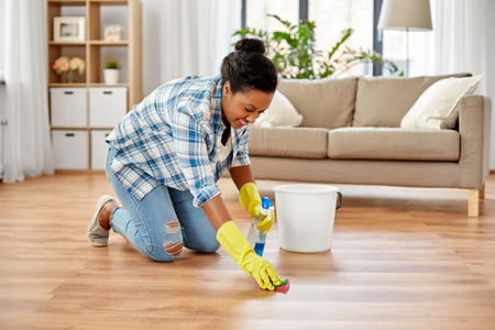 People, housework and housekeeping concept - African american woman in rubber gloves with sponge and detergent cleaning floor at home Stock Photo