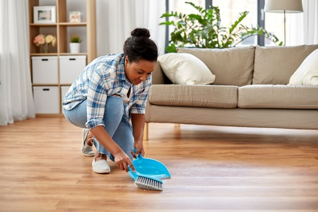 People, housework and housekeeping concept - African american woman with brush and dustpan sweeping floor at home