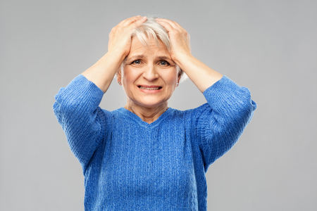 Stress, emotions and old people concept - portrait of stressed senior woman in blue sweater holding to her head over grey background Imagens