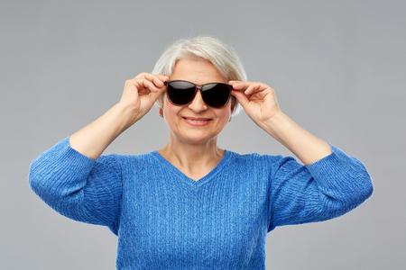 Valentines day, summer and old people concept - portrait of smiling senior woman in red black sunglasses over grey background