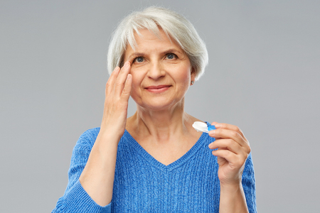 Health, vision and old people concept - senior woman putting on contact lenses over grey background