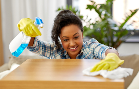 Household, cleaning and people concept - happy African american woman or housewife with spray detergent wiping table by paper tissue or rag at home