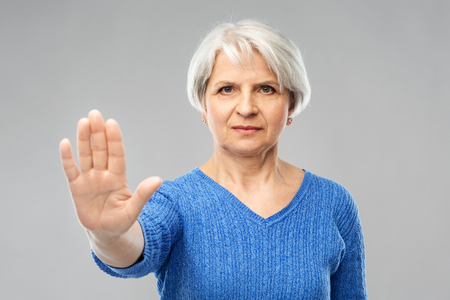 Gesture and old people concept - portrait of senior woman in blue sweater making stop gesture over grey background