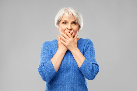 Emotion, expression and old people concept - portrait of confused senior woman in blue sweater covering her mouth by hands over grey background