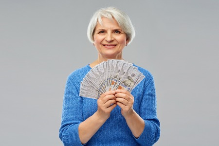 Savings, finances and people concept - smiling senior woman holding hundreds of dollar money banknotes 写真素材