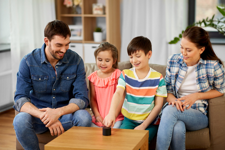 Family, technology and internet of things concept - happy father, mother, little son and daughter with smart speaker at home