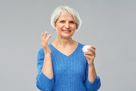 Beauty, old age and cosmetics concept - smiling senior woman with jar of face cream over grey background Foto de archivo - 122308204