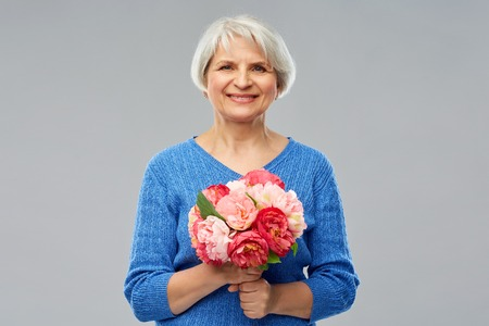 Holidays, old age and people concept - happy smiling senior woman with flowers over grey background Stock Photo
