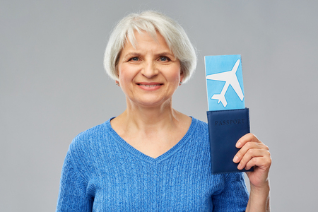 Tourism, travel and vacation concept - happy senior woman with passport and airplane ticket over grey background
