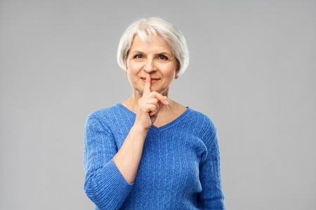Silence, censor and old people concept - portrait of smiling senior woman in blue sweater making shush gesture over grey background