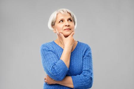 Alte Leute und Entscheidungsfindungskonzept - Porträt einer älteren Frau im blauen Pullover, die über grauen Hintergrund denkt
