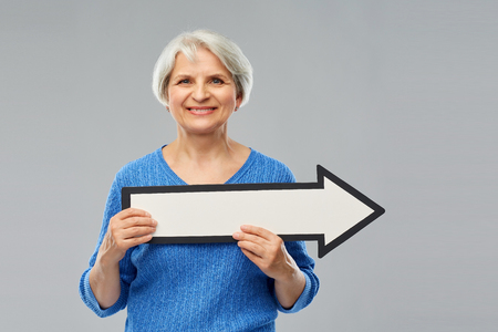 Direction and old people concept - smiling senior woman in blue sweater holding big white rightwards thick arrow over grey background