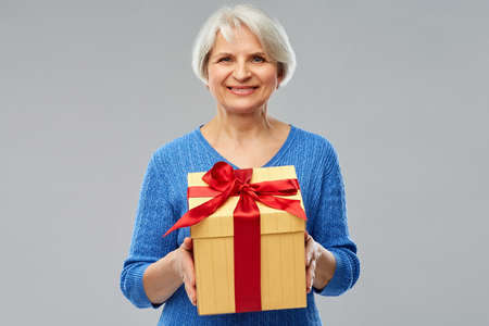 Holidays, old age and people concept - happy smiling senior woman with gift box over grey background
