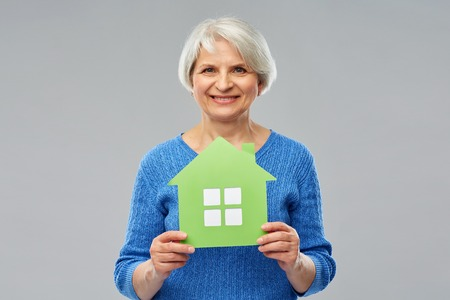 Home, environment and ecology concept - portrait of smiling senior woman holding green house icon over grey background