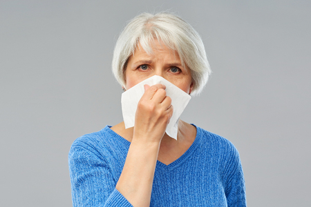 Health care, flu, and hygiene concept - sick senior woman blowing nose to paper napkin over grey background