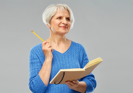 Inspiration, memoirs and old people concept - portrait of smiling senior woman in blue sweater with diary or notebook and pencil over grey background Imagens