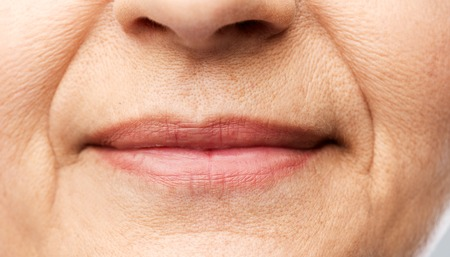 Beauty, body part and old age concept - close up of senior woman lips