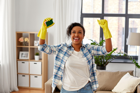 Cleaning, housework and housekeeping concept - happy African american woman in rubber gloves with sponge at home