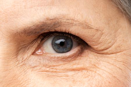 Visie, schoonheid en ouderdom concept - close-up van senior vrouw eye Stockfoto