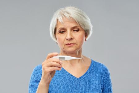 Koncepcja zdrowia i gorączki - chora starsza kobieta z termometrem na szarym tle