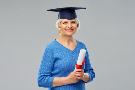 Graduation, education and old people concept - happy senior graduate student woman in mortar board with diploma over grey background