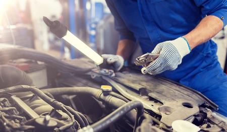 mechanic man with pliers repairing car at workshop 版權商用圖片