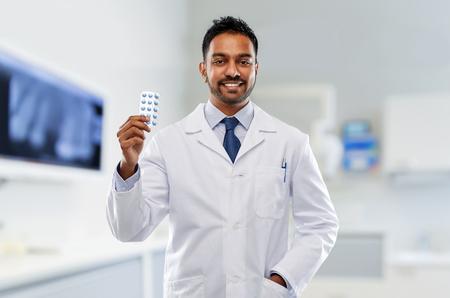 Indiase mannelijke tandarts met pillen bij tandheelkundige kliniek