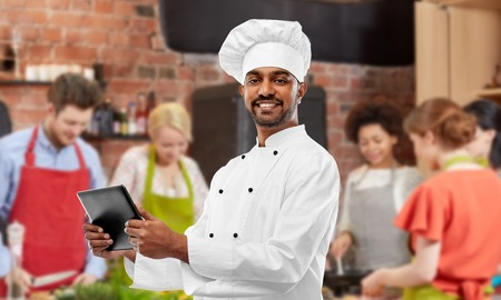 male indian chef with tablet pc at cooking class Stock Photo