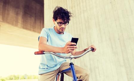 Hombre con smartphone y bicicleta de piñón fijo en la calle Foto de archivo