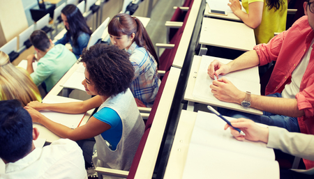 education, high school, university, learning and people concept - group of international students in lecture hall