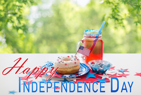 american independence day, celebration and holidays concept - close up of glazed sweet donut with flag and candies in disposable tableware at 4th july party over natural summer green background