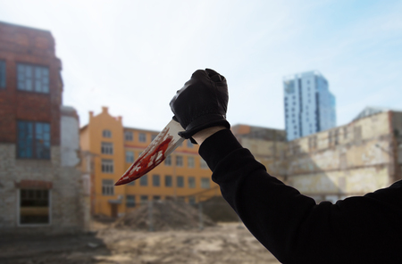 crime scene, murder and killing concept - close up of criminal or murderer hand in leather glove with blood on knife over city ruins background (staged photo)