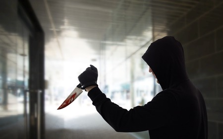 crime scene, murder and killing concept - close up of criminal or murderer with blood on knife over dark tunnel background