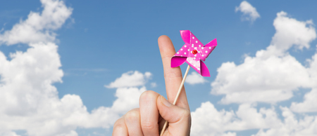 childhood and body part concept - close up of hand holding pinwheel toy over blue sky and clouds background