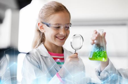 education, science and children concept - girl with magnifier studying test tube with chemical at school laboratory
