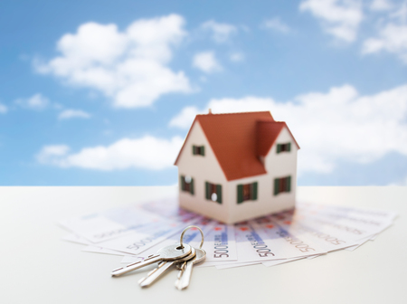 mortgage, real estate and property concept - close up of home model, money and house keys over blue sky and clouds background