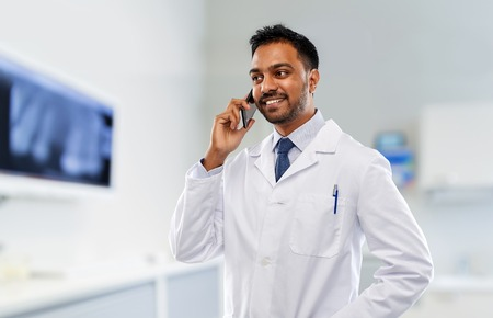 medicine, dentistry and healthcare concept - smiling indian male dentist in white coat calling on smartphone over dental clinic office background Stock Photo