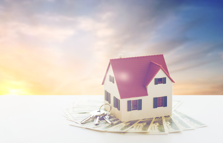 mortgage, real estate and property concept - close up of home model, money and house keys over sunset sky background Stock fotó